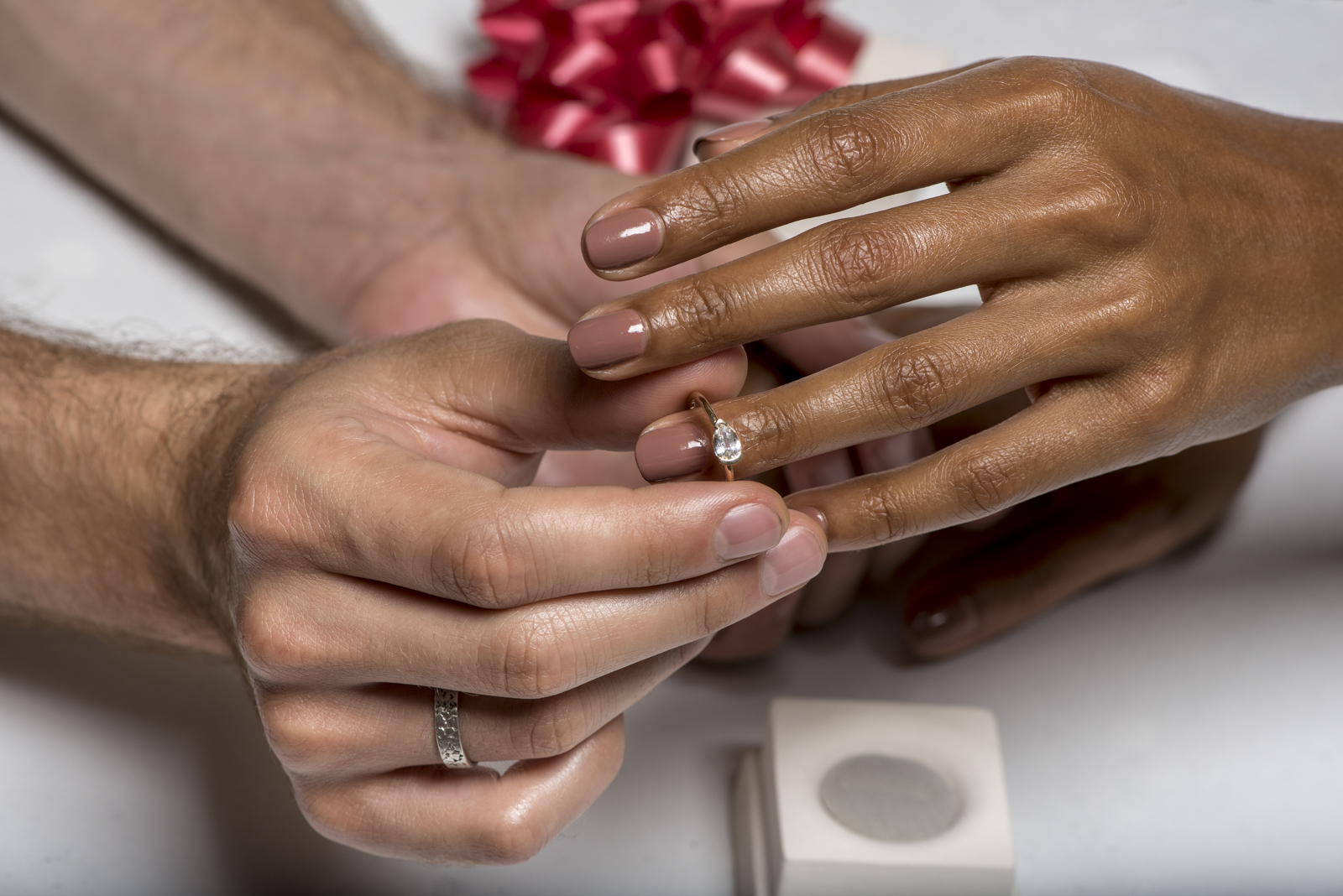 Photograph of a man placing an engagement ring on a woman's finger